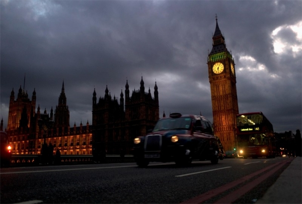 a-taxi-pass-big-ben-on-westminster-bridge-in-london